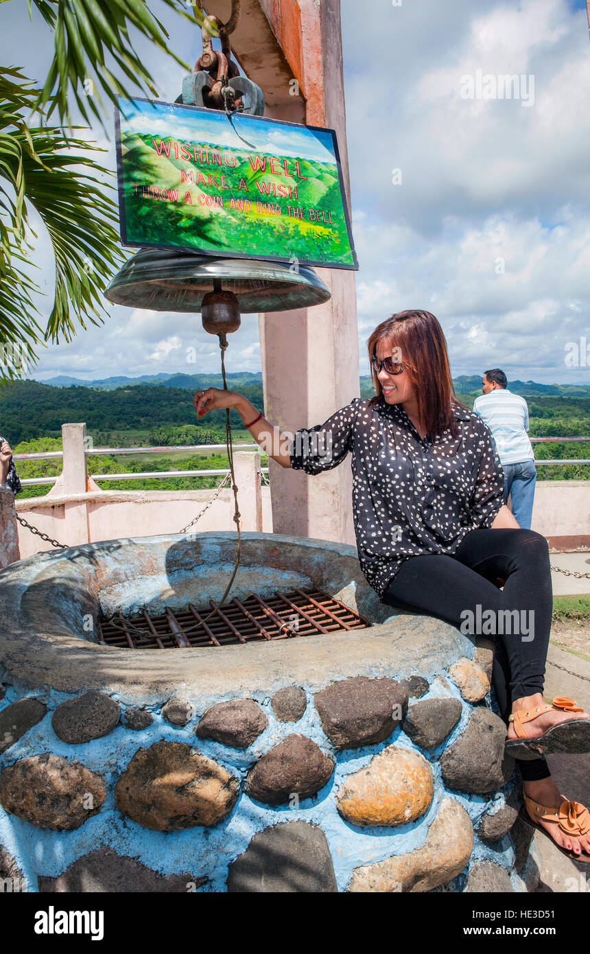 A tourist drops coins into the wishing well at the Chocolate Hills Monument on Bohol Island, Philippines. - Stock Image