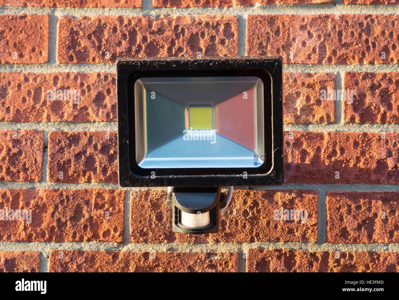 LED security floodlight with integral PIR motion sensor mounted on an external brick wall. England, UK. - Stock Image