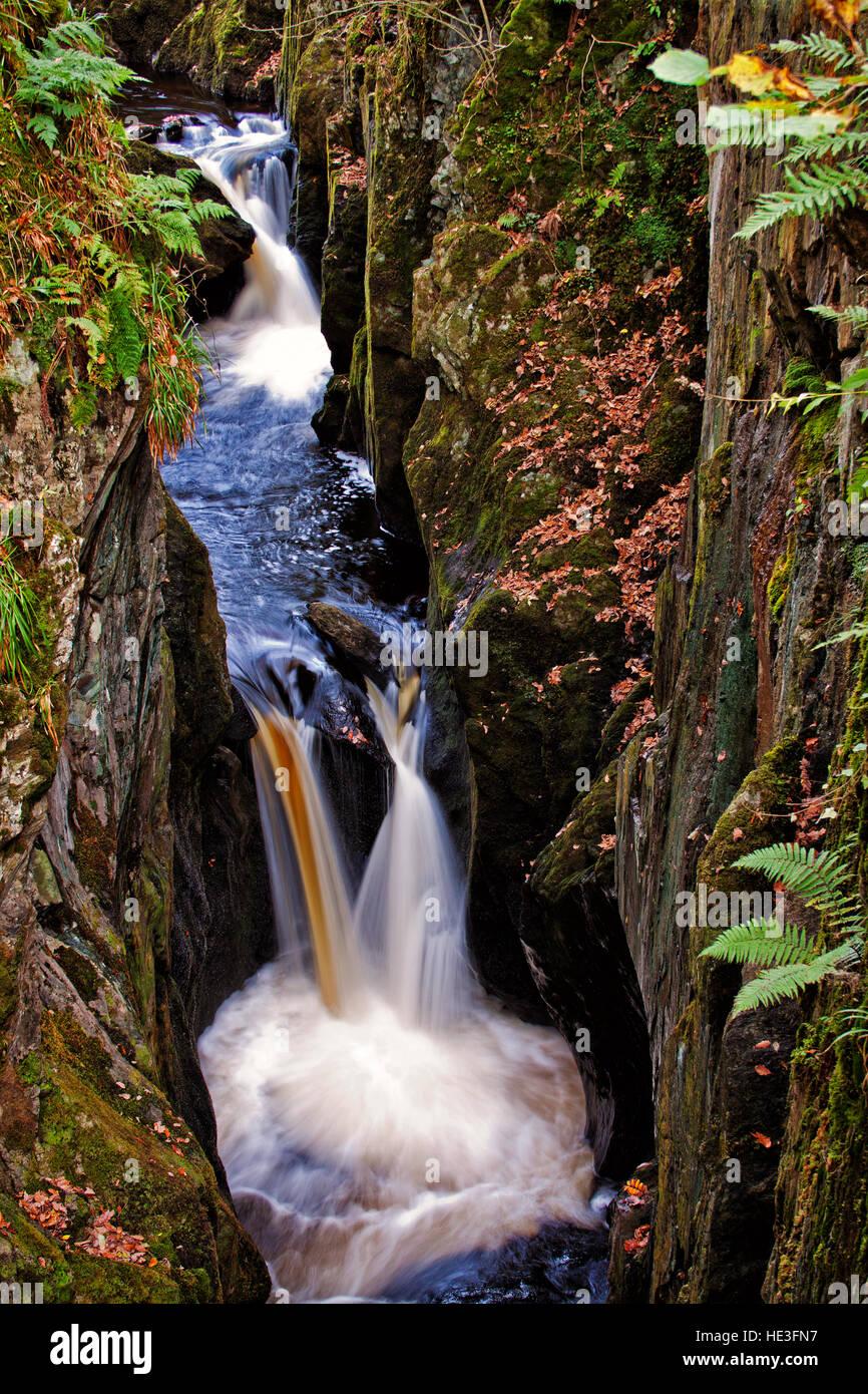 Snow falls flow through a narrow gully of rock - Stock Image