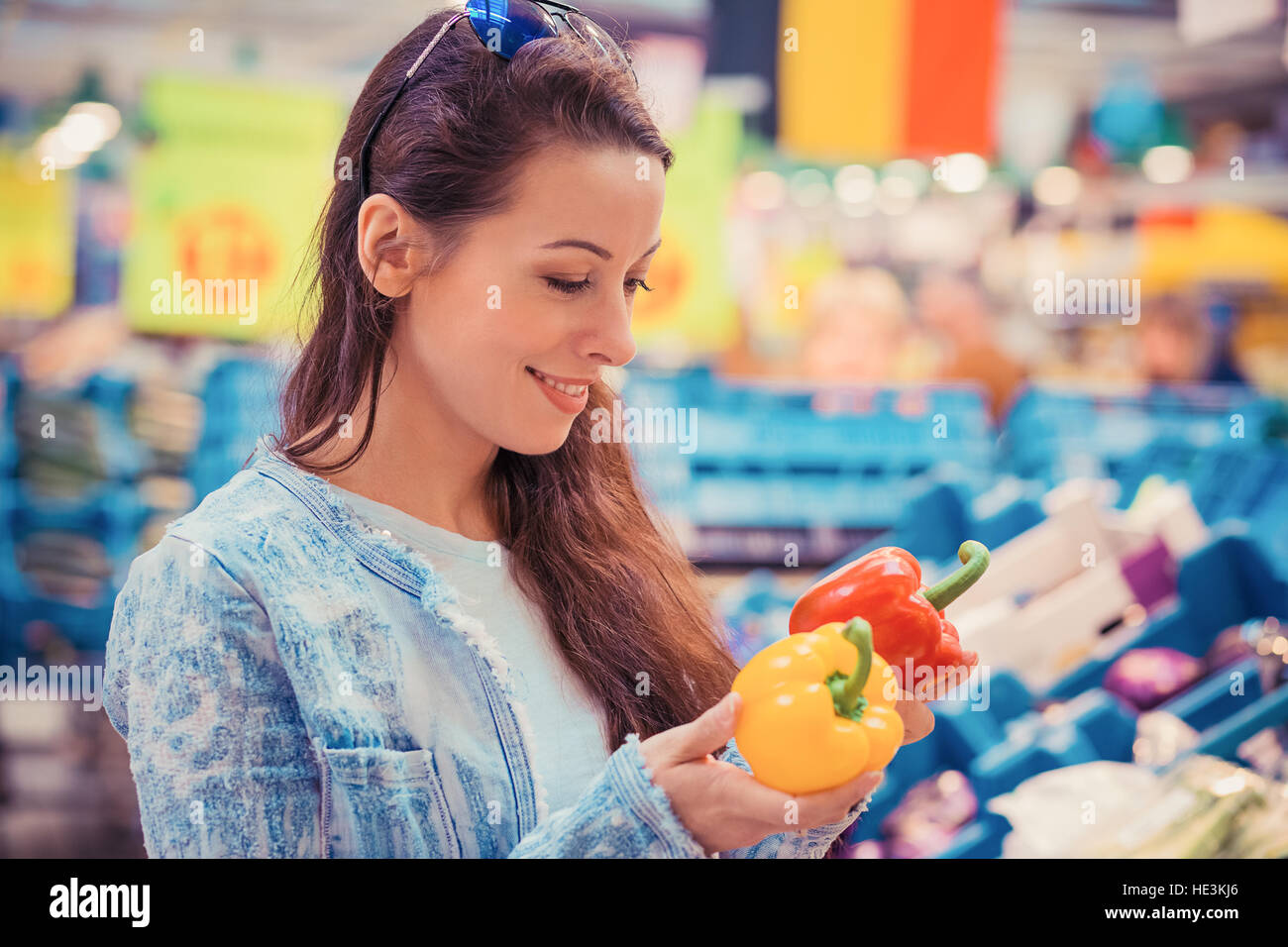 Closeup portrait, beautiful, pretty young woman picking up, choosing bell peppers vegetables in grocery store supermarket - Stock Image
