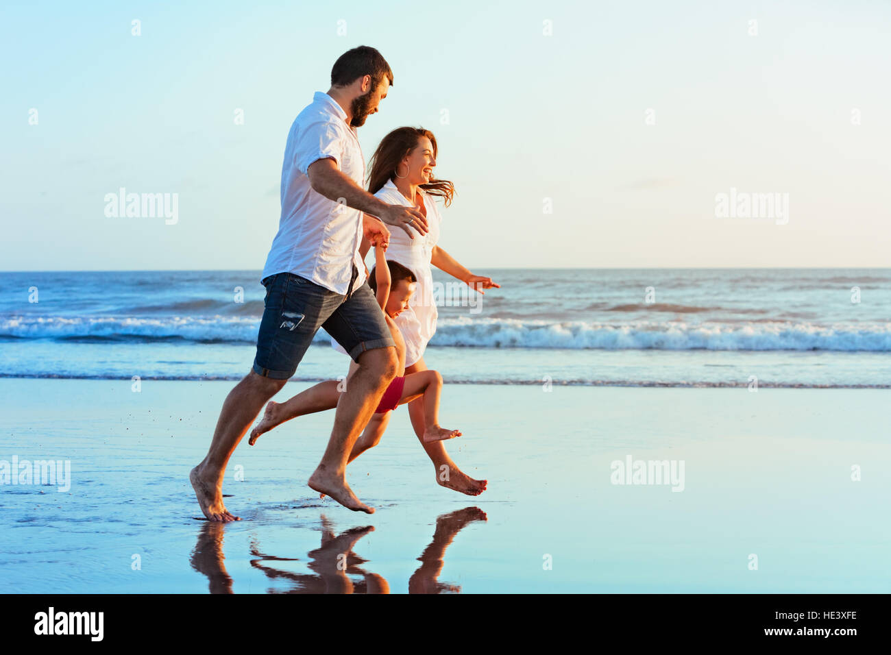 Happy family - father, mother, baby son hold hands, run together by water pool along sea surf on sunset black sand - Stock Image