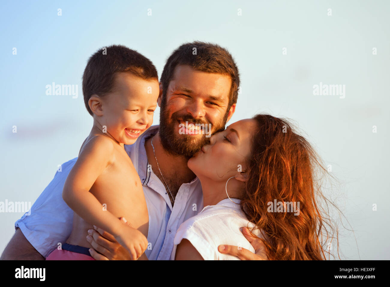Face portrait of hugging beautiful family - happy mother, father holding baby son on hands walk with fun on sunset - Stock Image