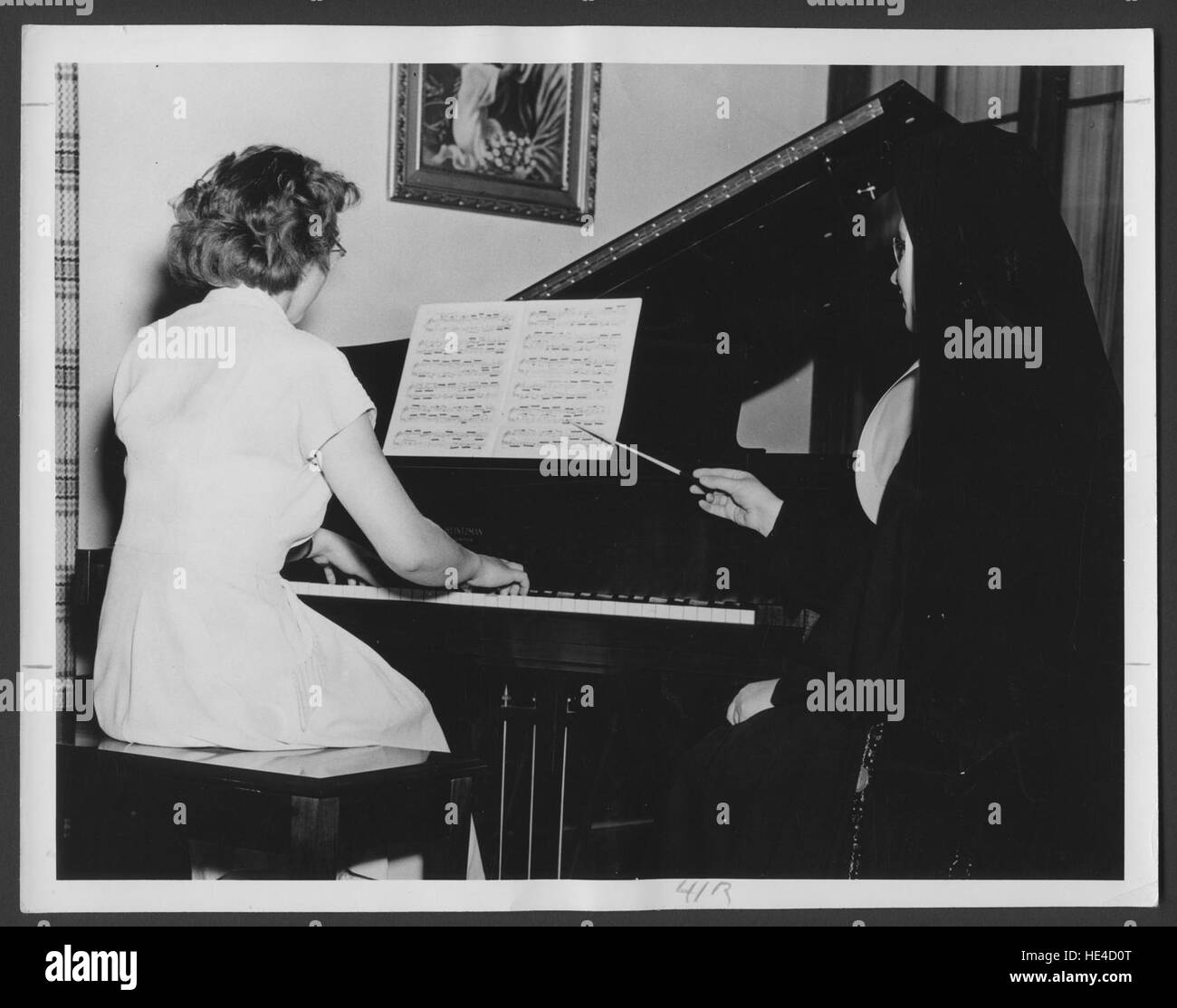 Sr. Callistus Arnsby teaching piano to a student at the Sacred Heart School of Music, predecessor to the St. Joseph's - Stock Image