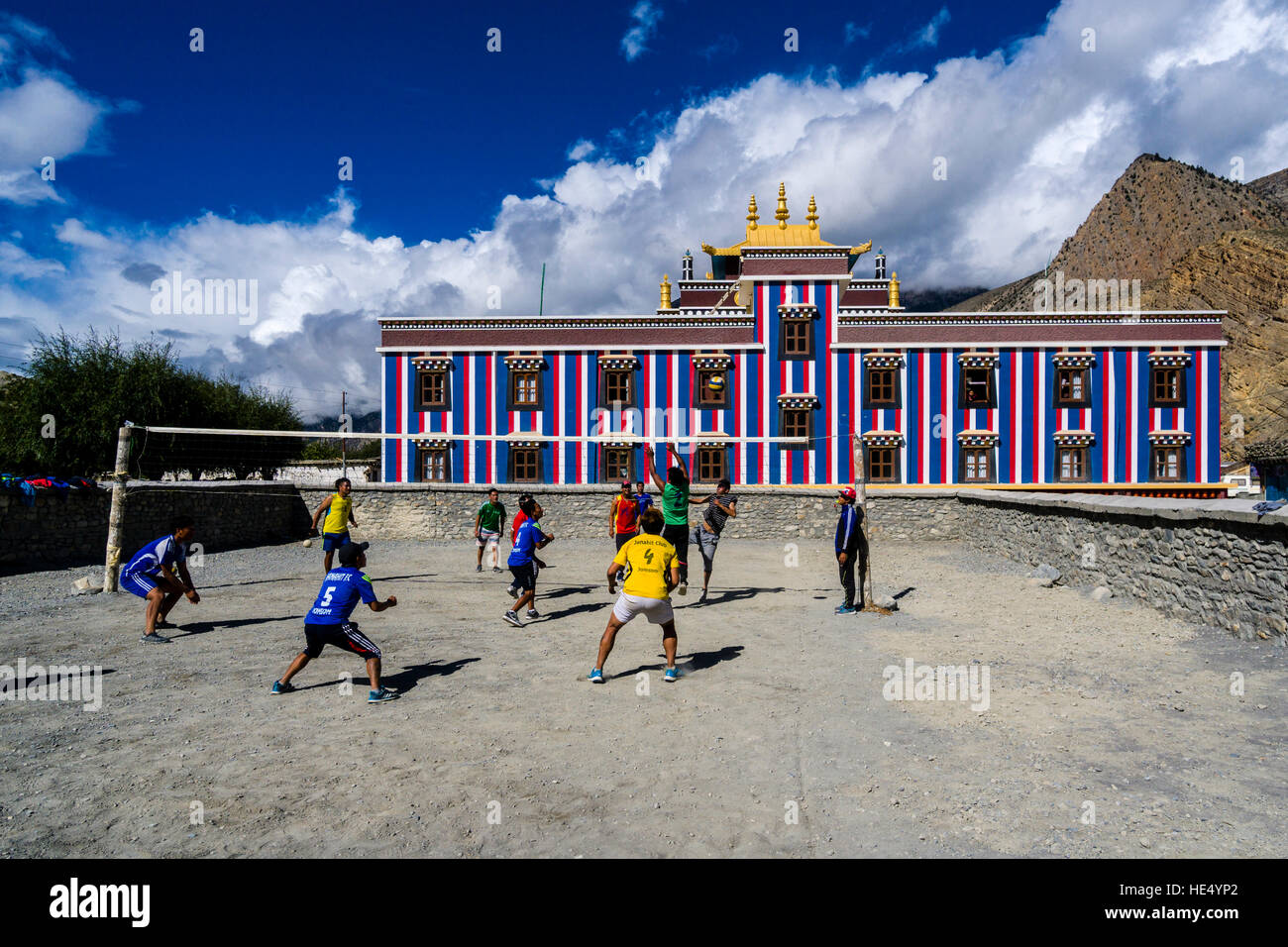 Some young men are playing volleyball in front of the building Sakya Gompa - Stock Image