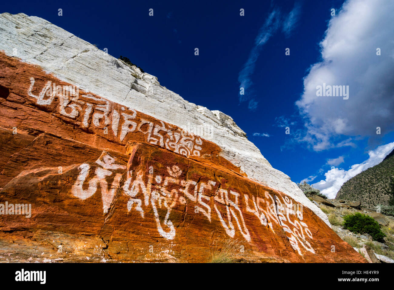 A rock above the village is painted red and white with some tibetan scriptures for religious reasons - Stock Image