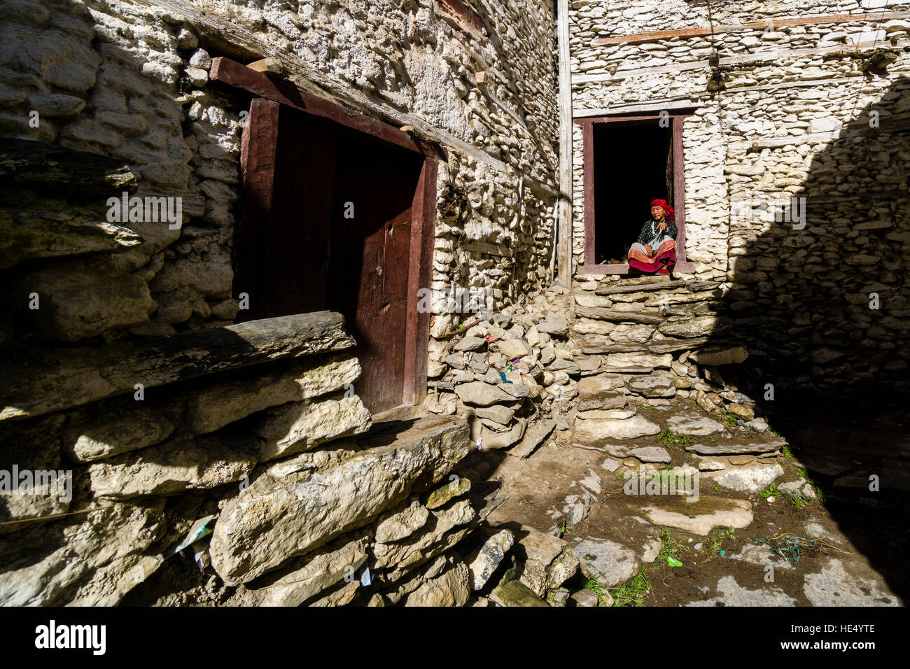 An old local farmers woman is sitting in the door of a stone house Stock Photo