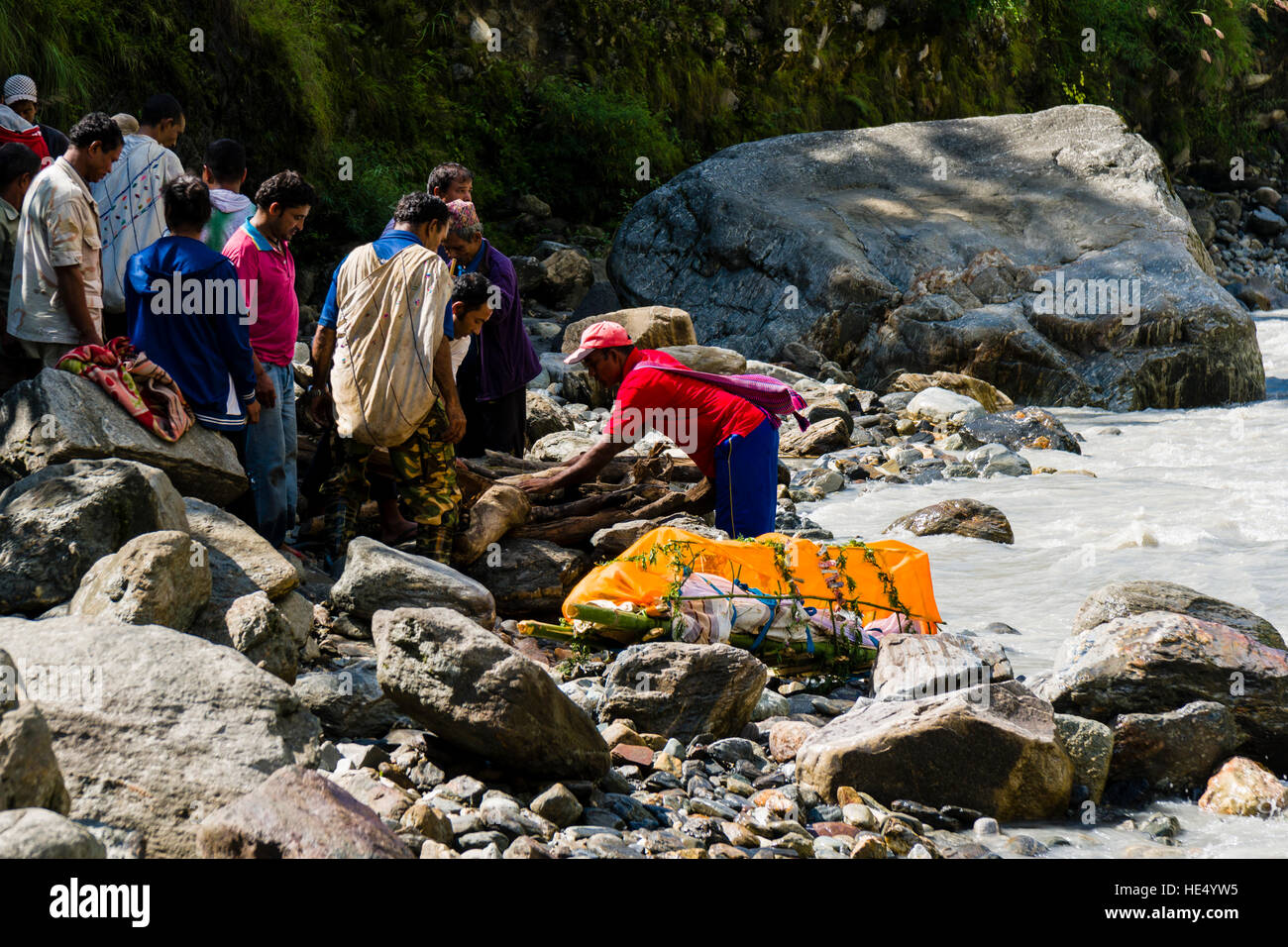 A group of local farmers are prepairing the funeral of a death body at the cremation ground on the bank of the river - Stock Image