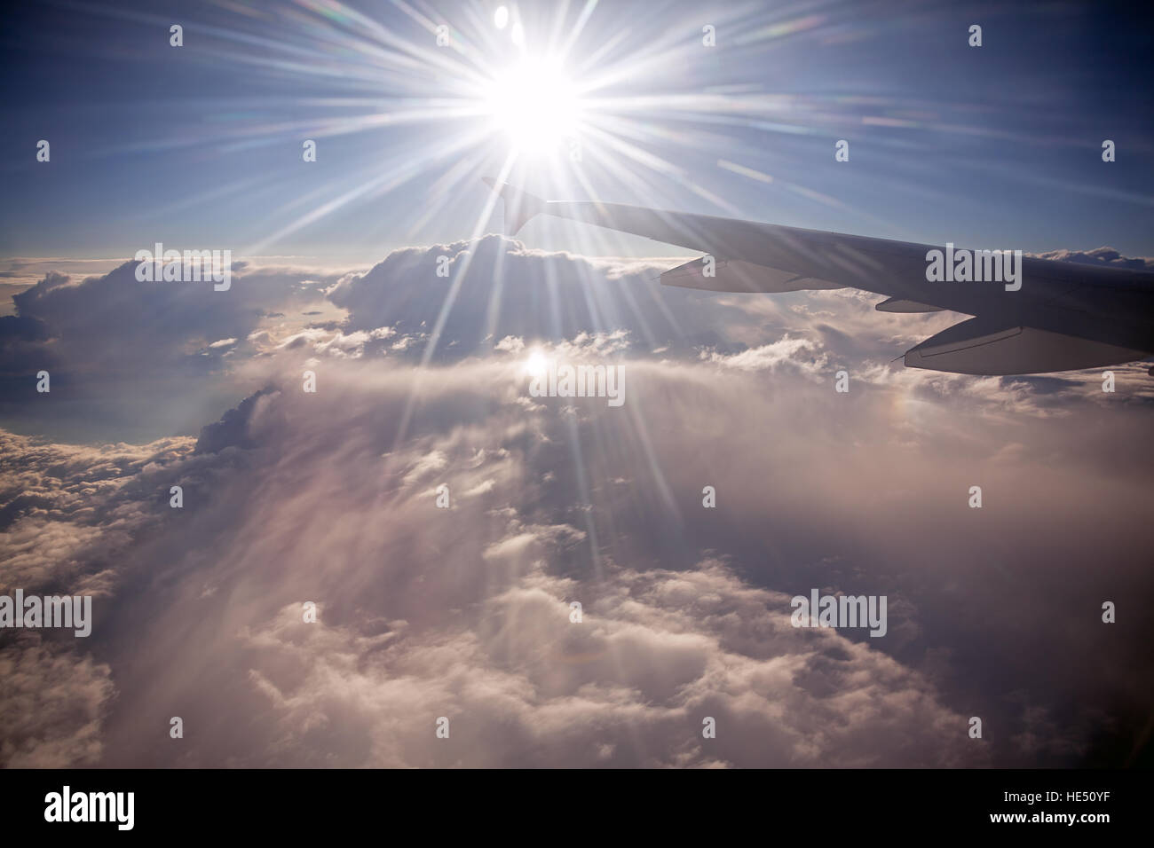 Wing of aircraft on the background of sunny rays and clouds. Fast aerial transport, traveling and voyage concept. Stock Photo
