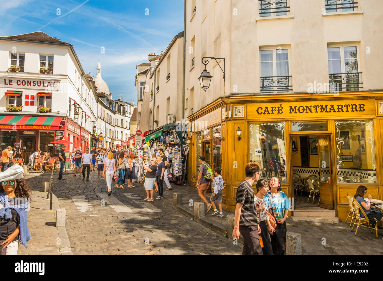 street scene montmartre district, tourists walking down cobblestone street - Stock Image