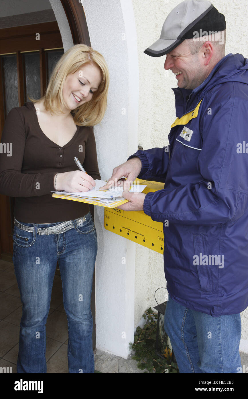 Woman signing for a parcel delivered by a postman, mailman - Stock Image