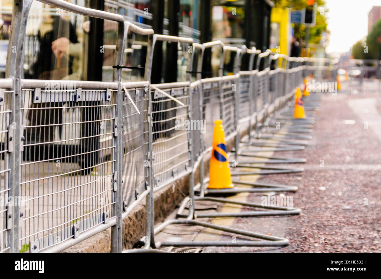 Crowd control barriers line a road to keep people back in advance of an event - Stock Image