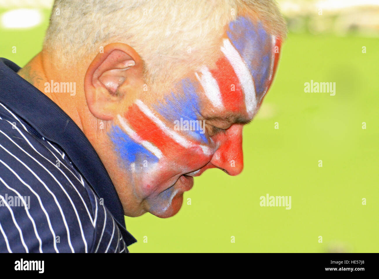 Middle aged man wearing union jack face paint during the Warsaw speedway grand prix in Poland - Stock Image