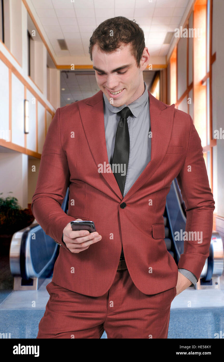 Handsome man using a cell phone for texting - Stock Image