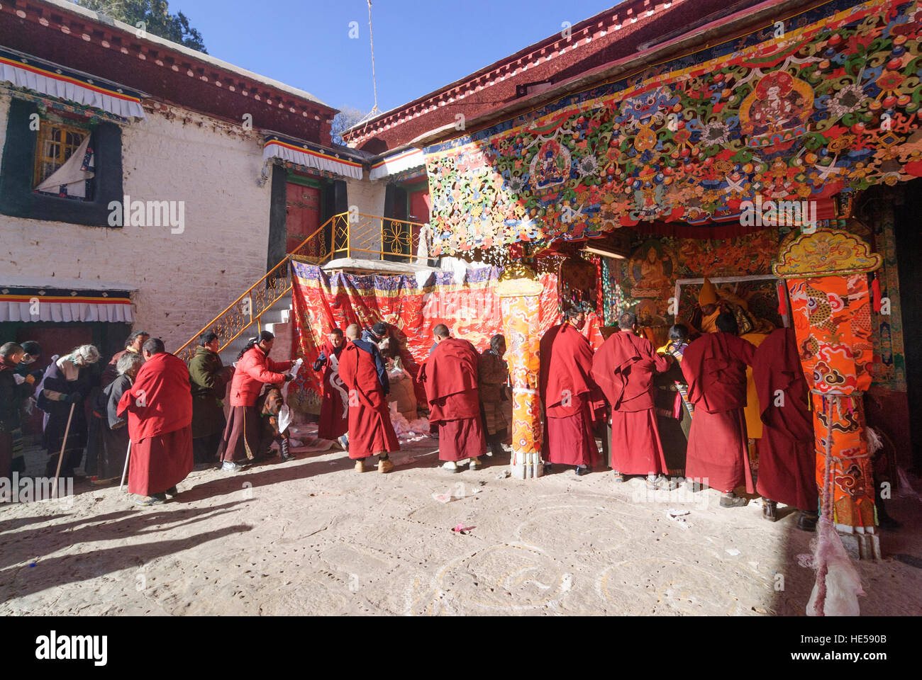 Lhasa: Monastery Sera; Pilgrims stand to receive the blessing of a lama, they get a push with a pillow on their - Stock Image