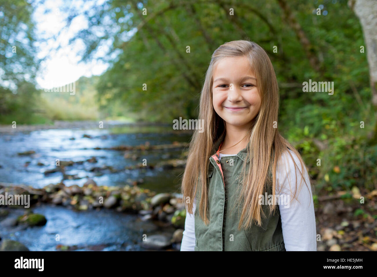 Young girl in a green vest posing for a lifestyle portrait outdoors along the banks of the McKenzie River in Oregon. - Stock Image