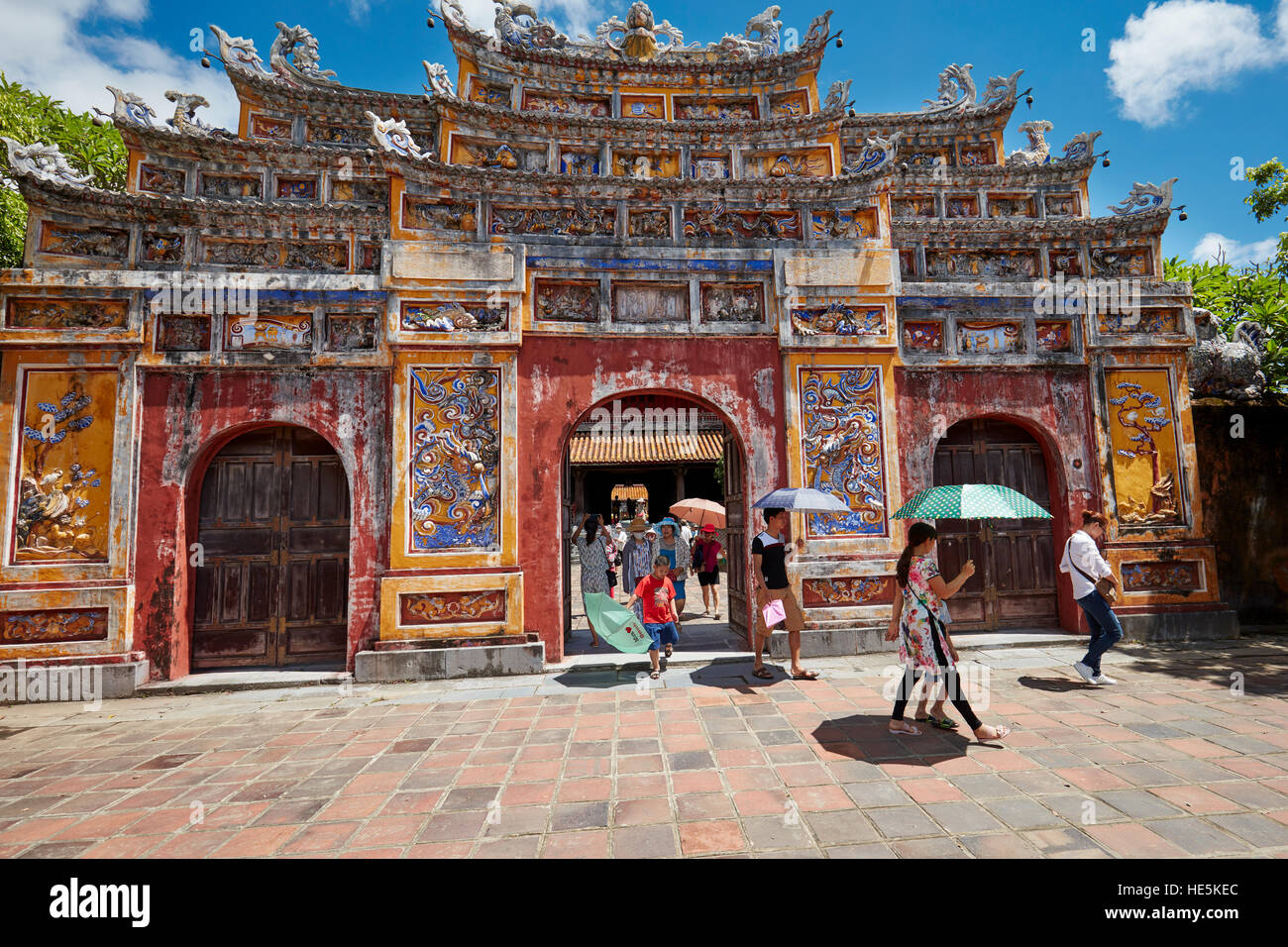 People walking out of entrance gate to The To Mieu Temple Compound. Imperial City (The Citadel), Hue, Vietnam. - Stock Image