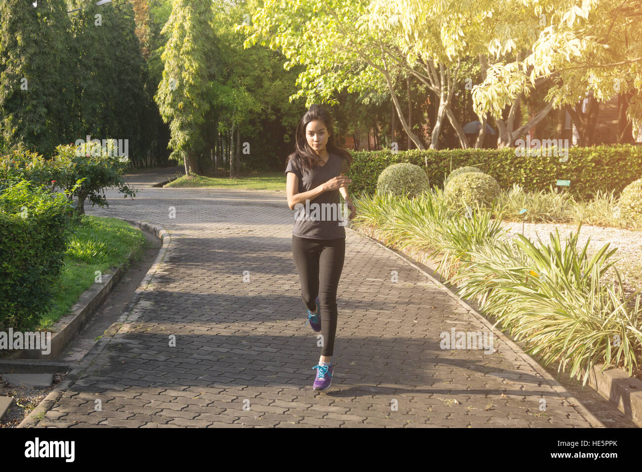Women runners sprinting outdoors. Sportive people in public park urban area healthy lifestyle and sport concepts. - Stock Image