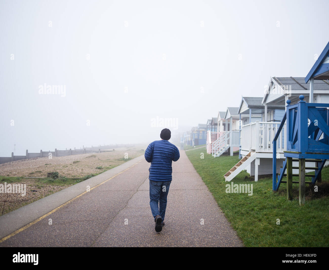 Whitstable, UK. 18th Dec, 2016. Weather in Kent. A local man walks along Tankerton promenade passing by the wooden Stock Photo