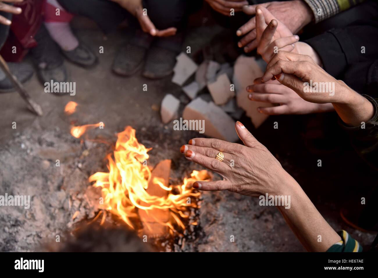 Aleppo, Syria. 18th Dec, 2016. Displaced Syrians make a fire to keep warm at the Jibreen temporary shelter, south - Stock Image