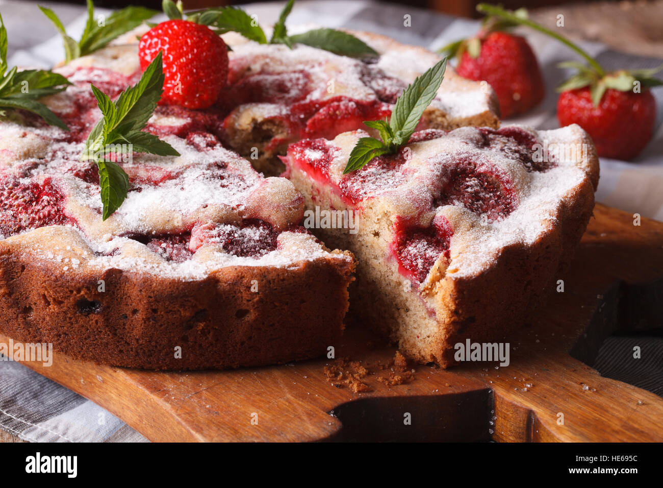 Home sliced strawberry pie with mint on a cutting board macro. Horizontal Selective Focus - Stock Image