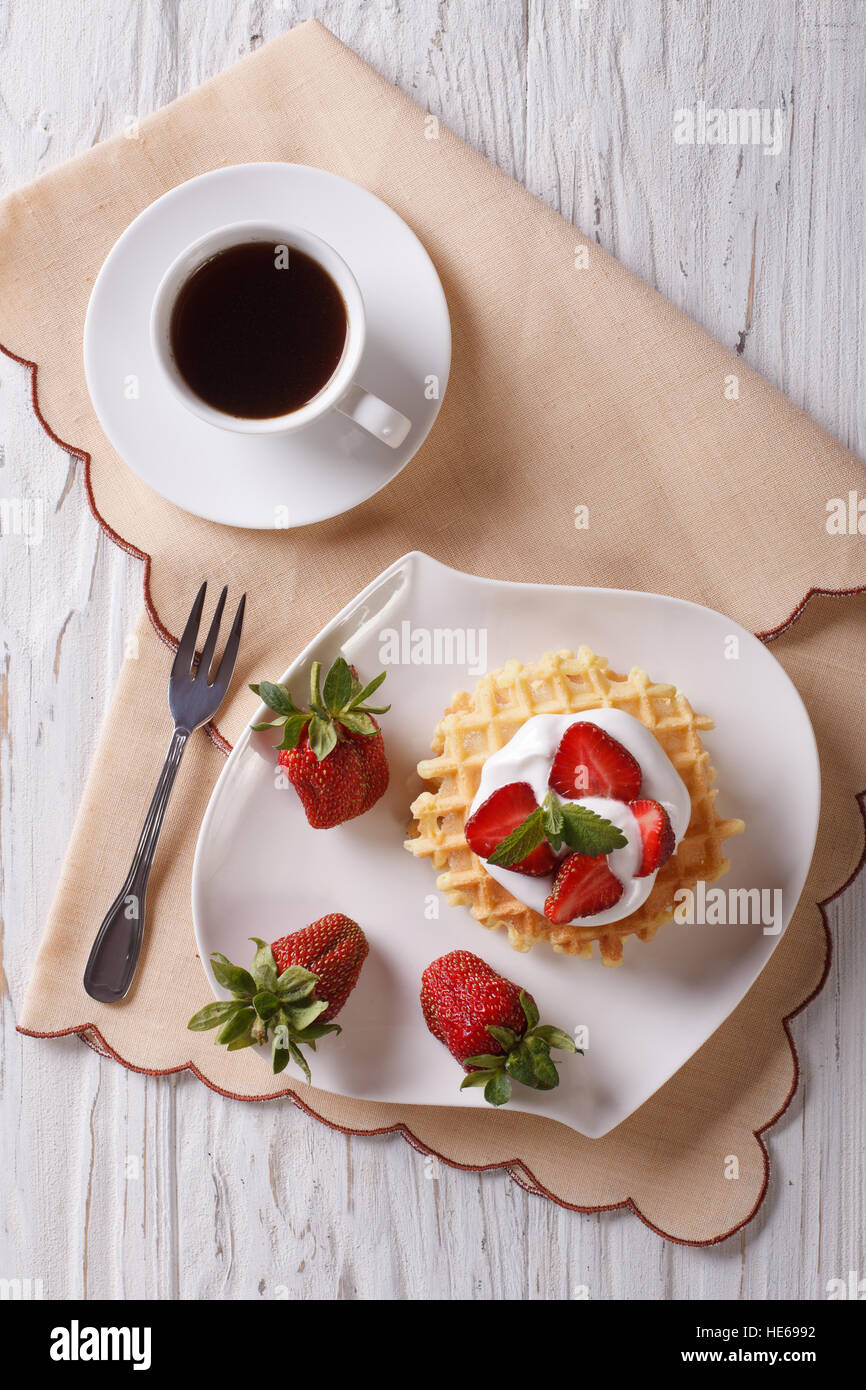waffles with fresh strawberries, cream and coffee on a table. vertical top view - Stock Image
