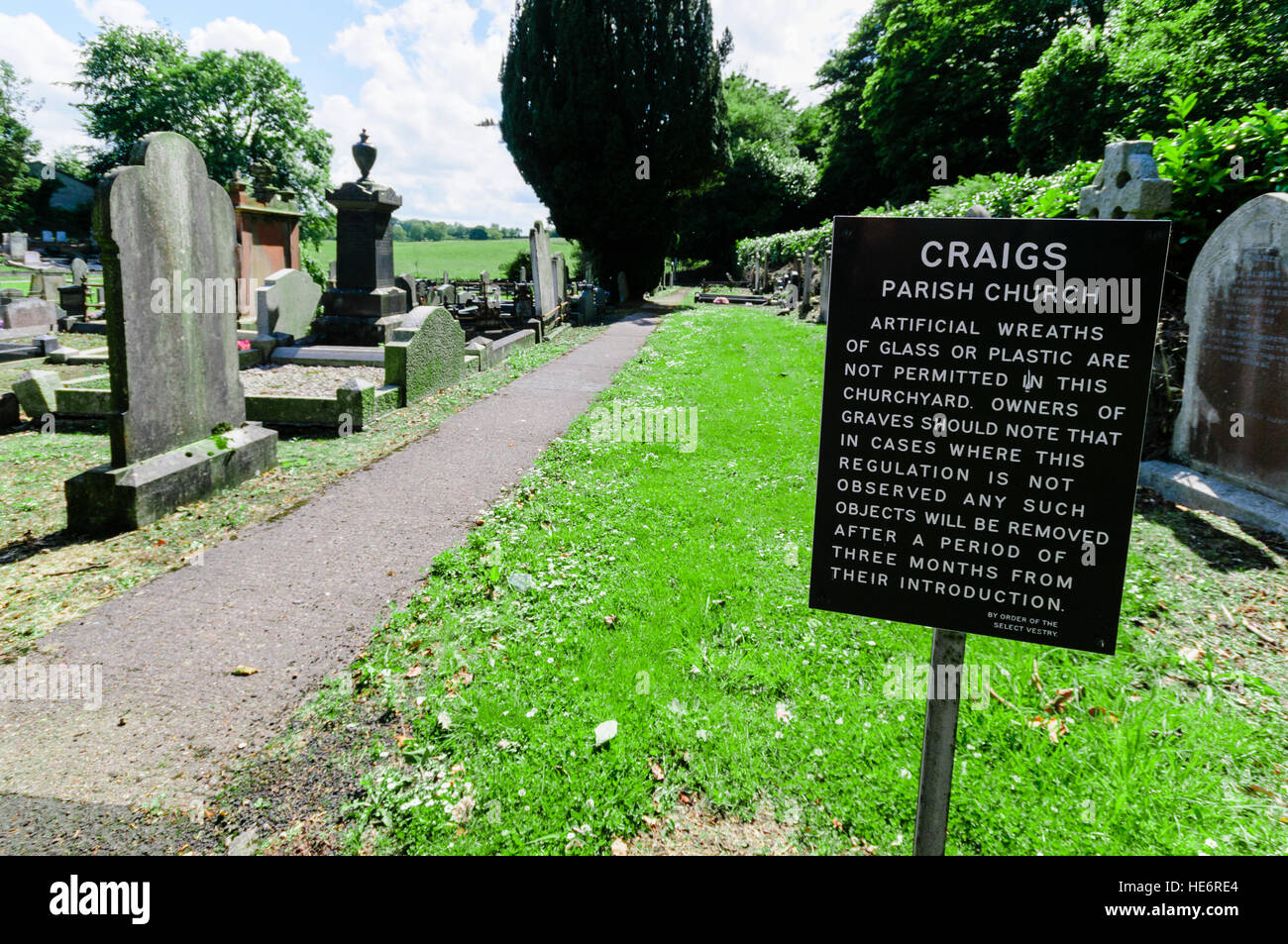 Sign in rural graveyard warning that plastic and glass wreaths are not permitted - Stock Image