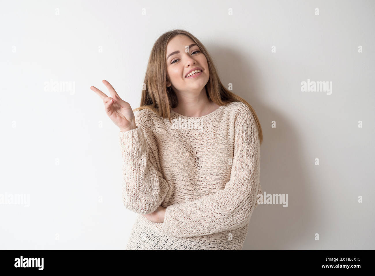 Funny girl showing the peace sign - Stock Image