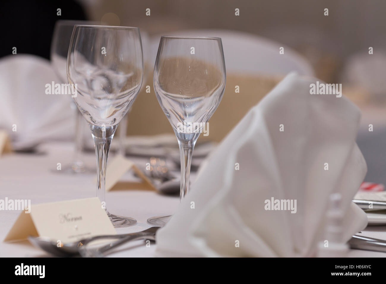 Dinner table set for wedding celebration with wine glasses, cutlery, white fan napkins and place name card - Stock Image