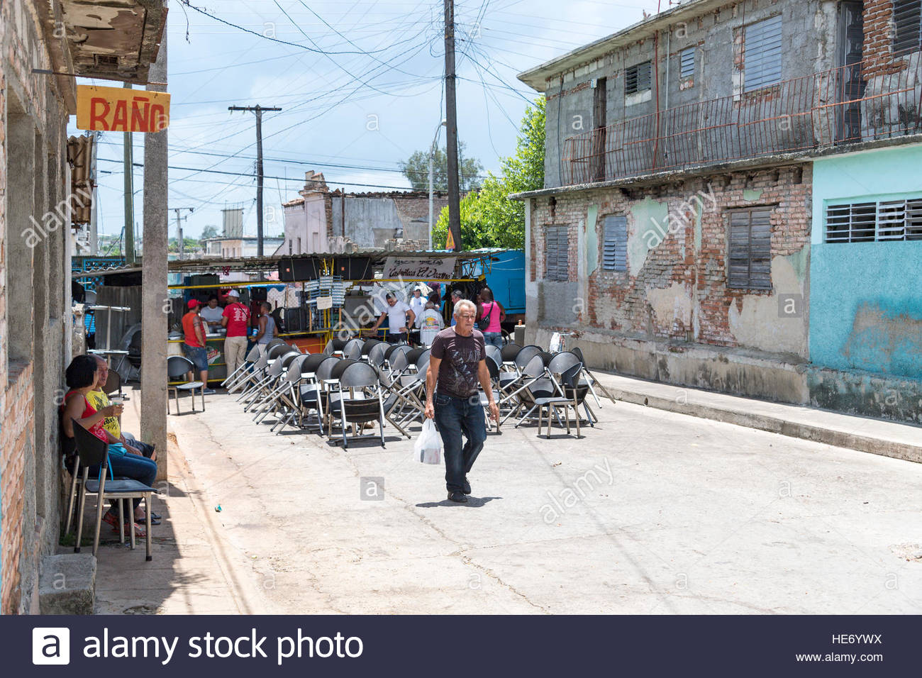Carnivals: renting washroom in private house close to a beer selling stand. Street eating joint in the background. - Stock Image