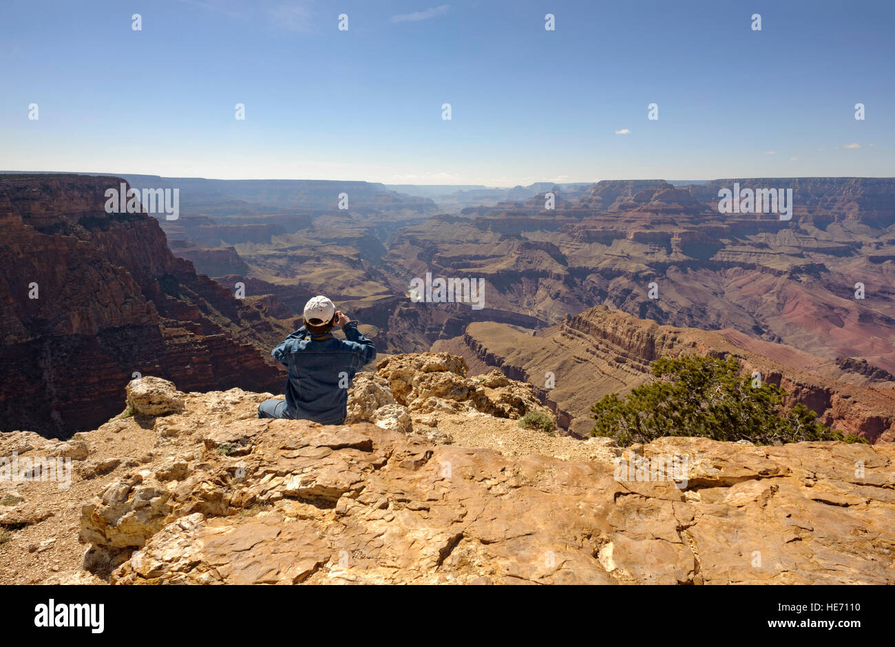 Adventure travel man at edge of the Grand Canyon south rim Pipe Creek Vista taking photo, Arizona USA rear view - Stock Image