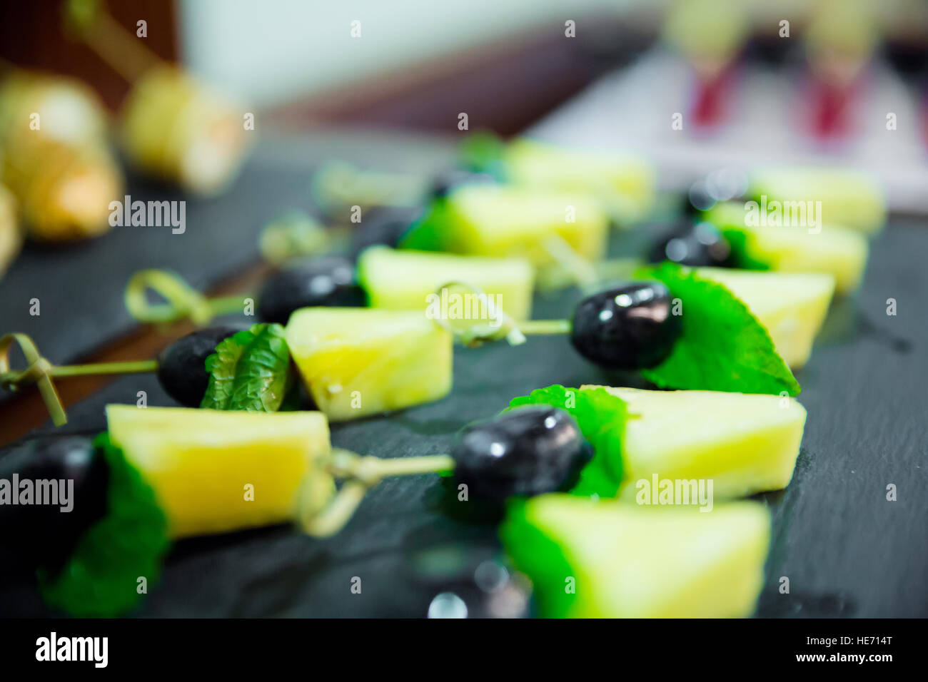 Blured cater canapes with pinapple and grapes on black table - Stock Image
