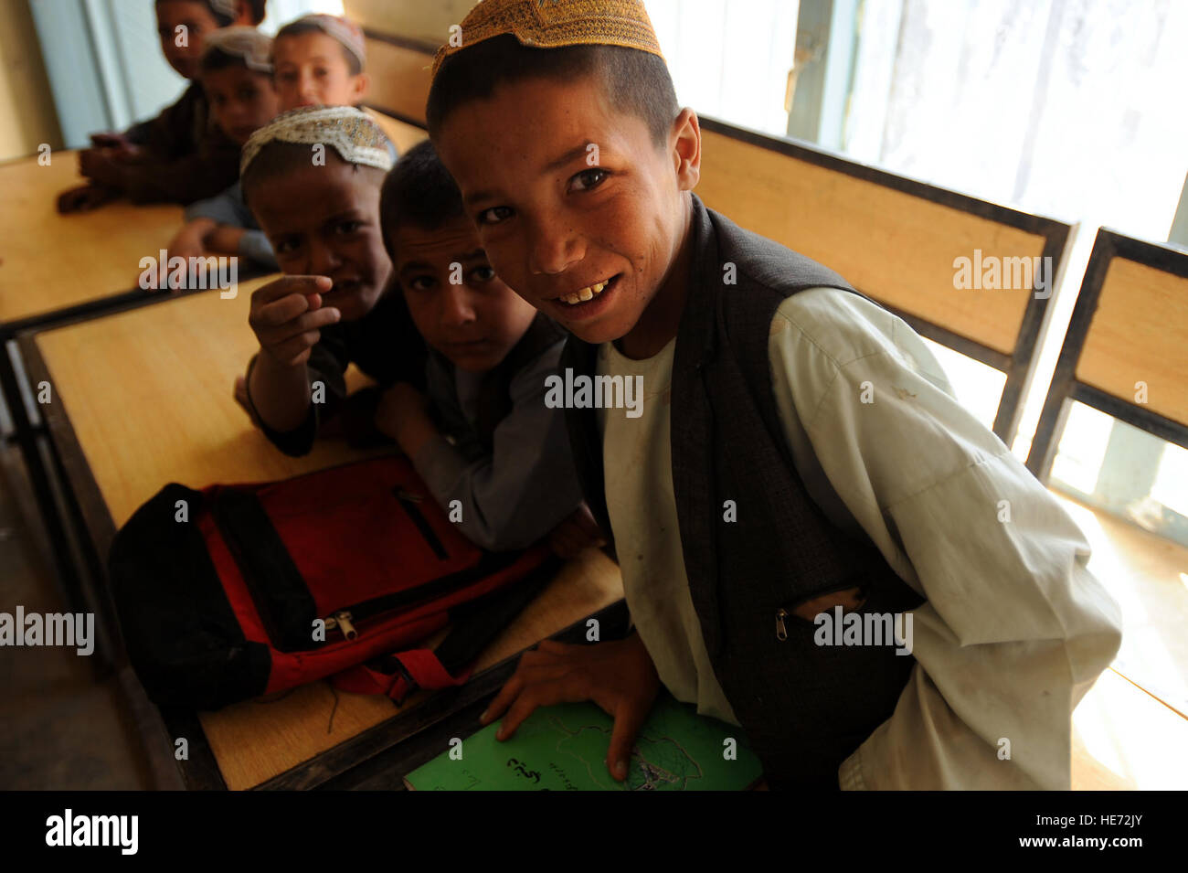 Young Afghan children lean over their desks at school to smile for the camera, March 31, Morgan Kacha village, Southern - Stock Image