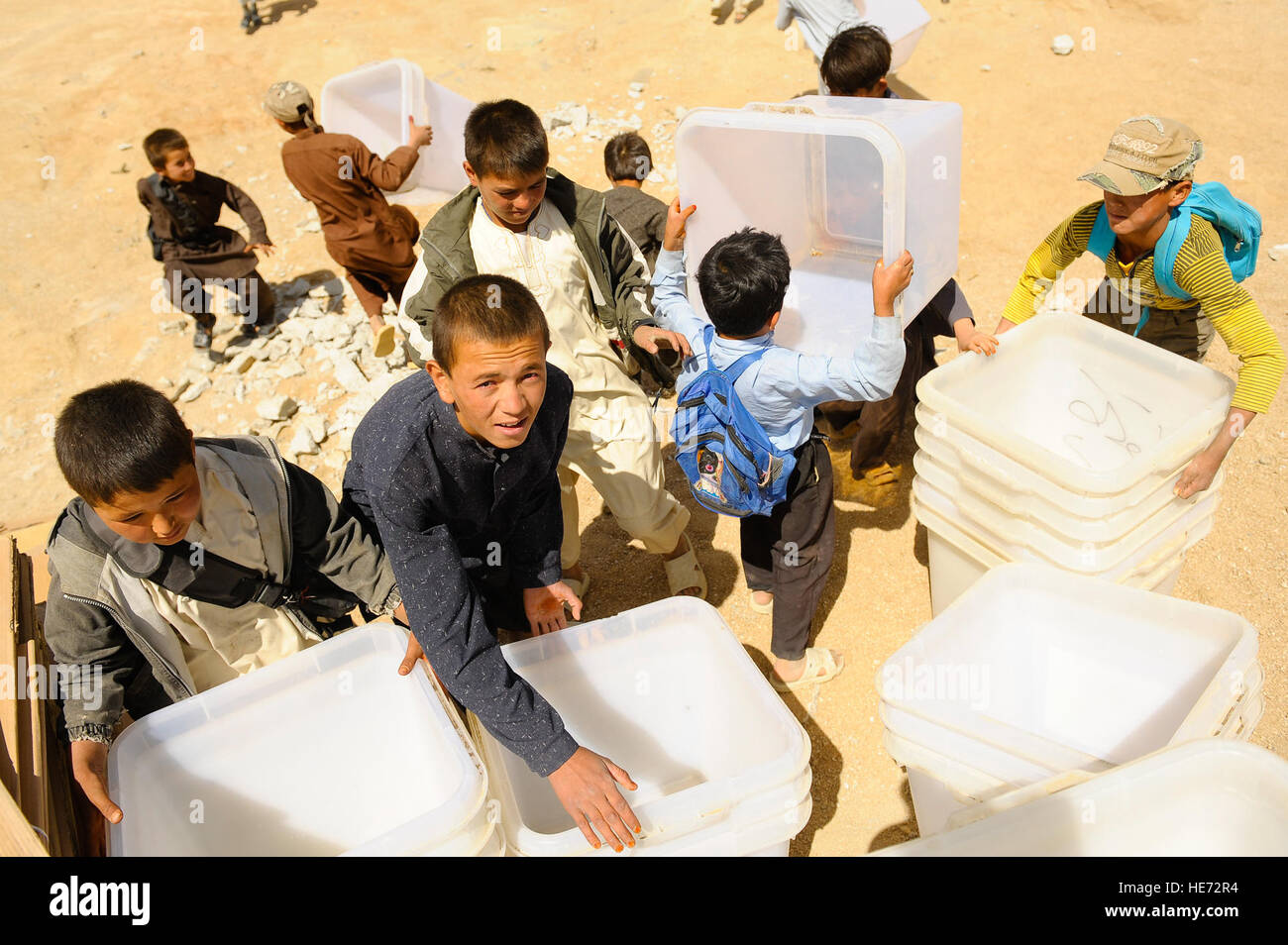 Afghan boys help unload ballot materials from an Mi-17 helicopter in Jaghuri, Afghanistan, Sept. 16, 2010.  The - Stock Image