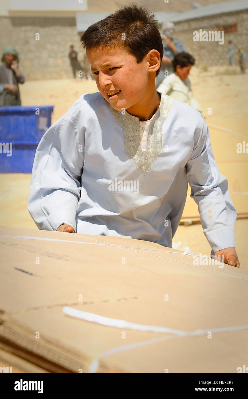 An Afghan boy helps unload ballot materials from an Mi-17 helicopter in Jaghuri, Afghanistan, Sept. 16, 2010.  The - Stock Image