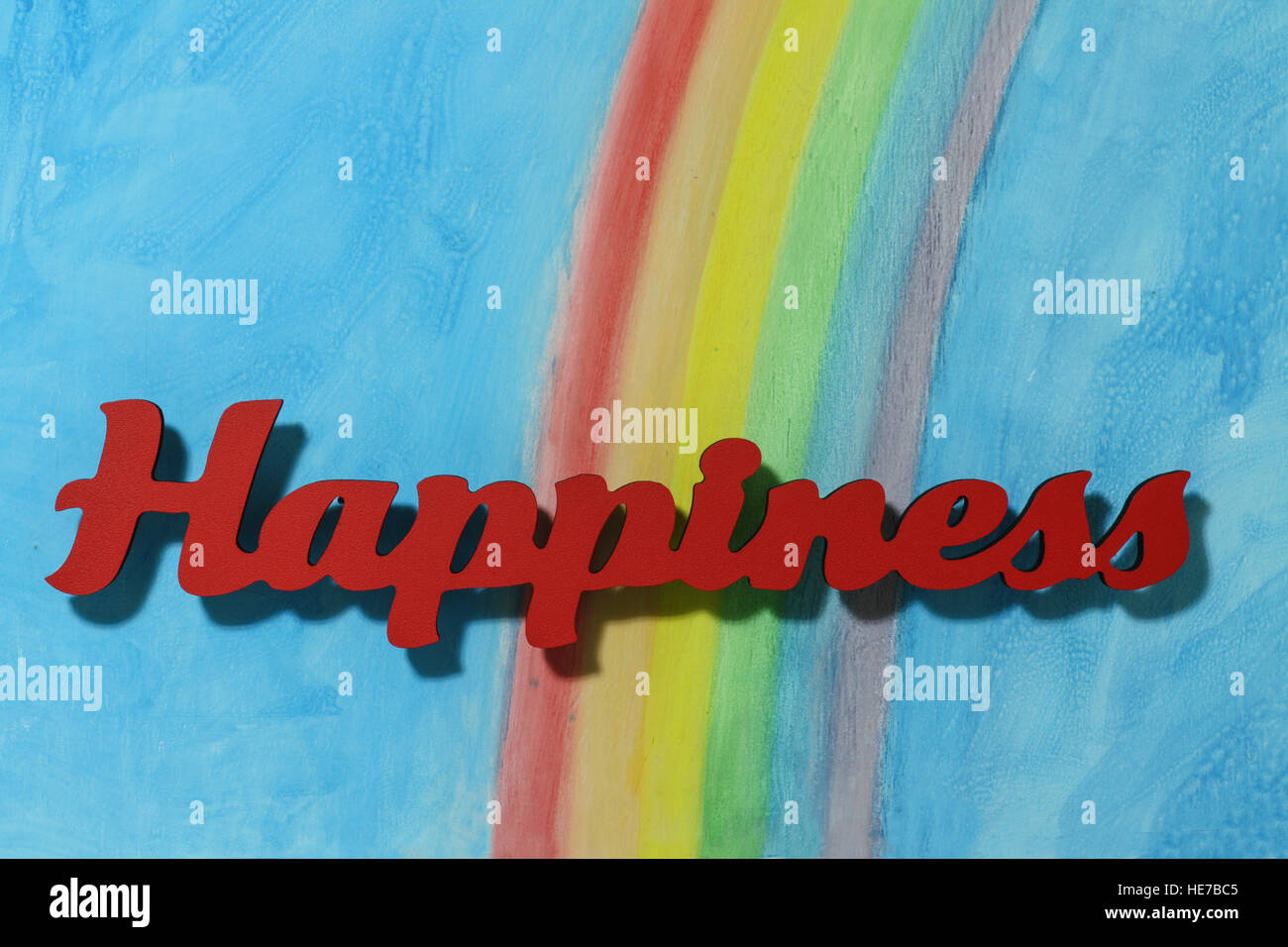 Red letters spelling the word happiness to illustrate the concept of joy, happy, love and wellness; close up. Stock Photo