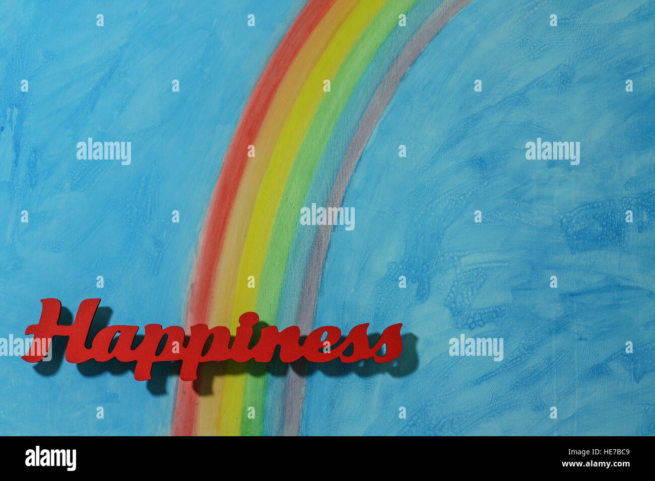 Red letters spelling the word happiness to illustrate the concept of joy, happy, love and wellness; landscape format. - Stock Image