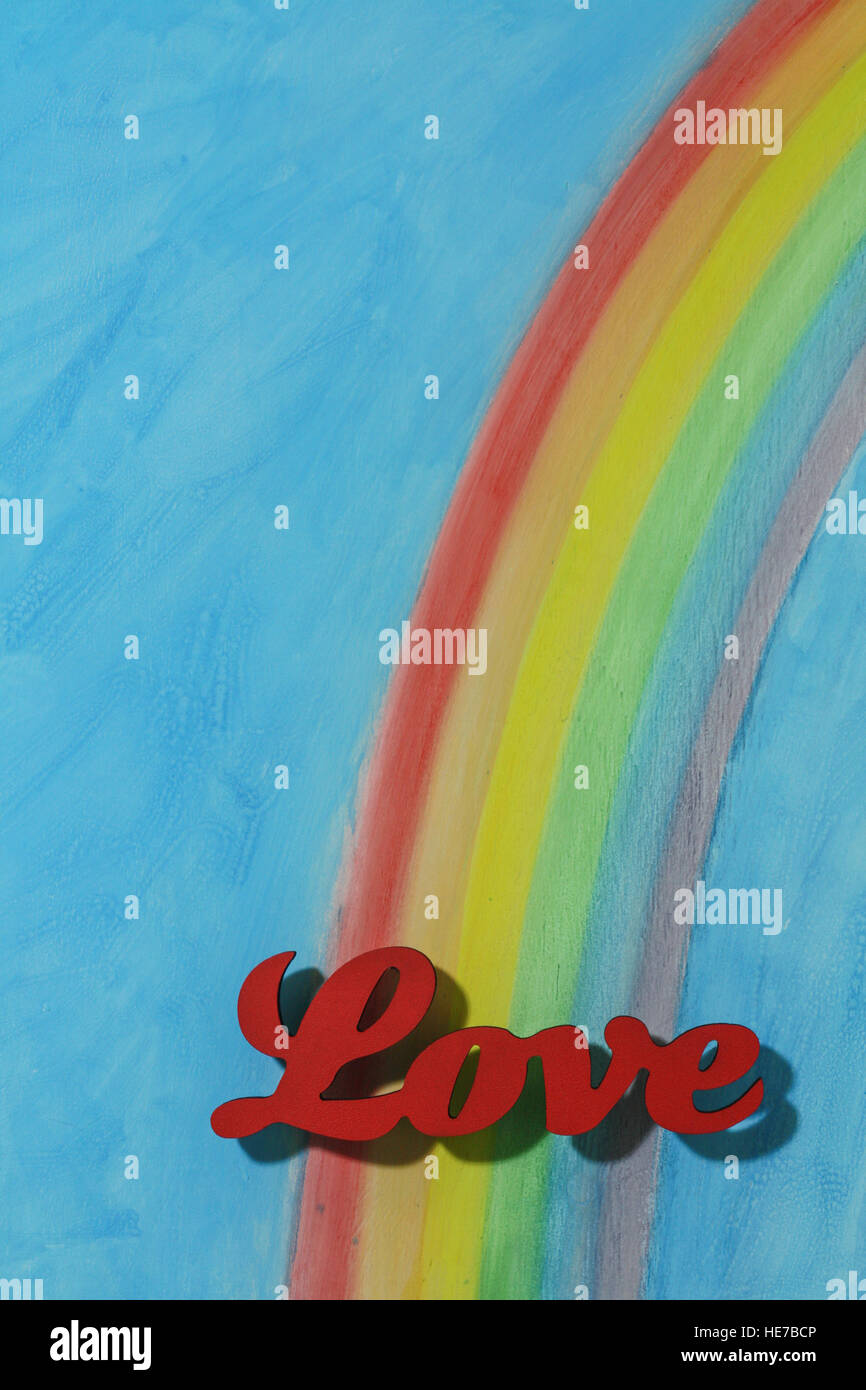 The word love with a background rainbow, illustrating the concept of love, lust, desire and joy; portrait format. - Stock Image