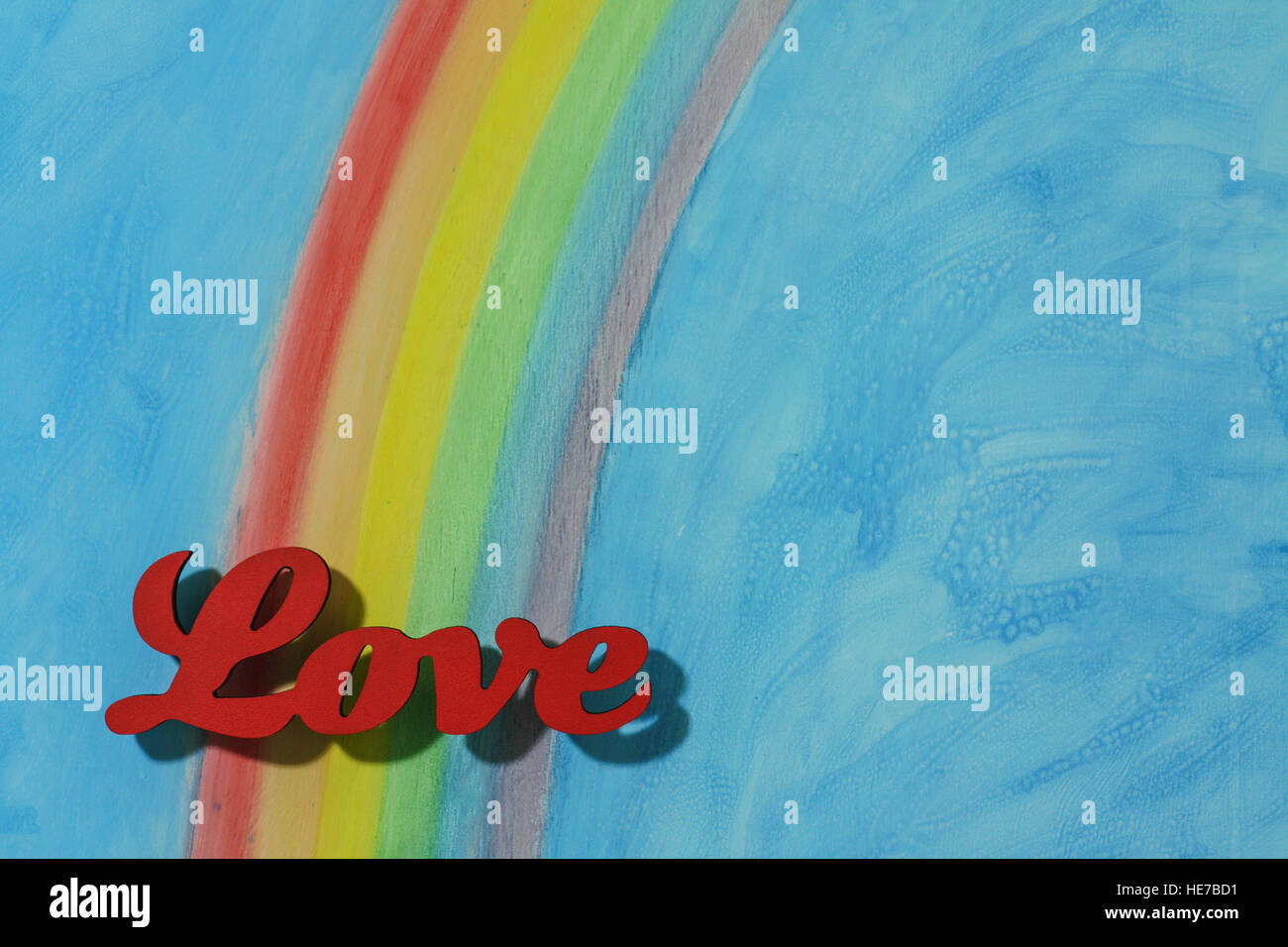 The word love with a background rainbow, illustrating the concept of love, lust, desire and joy in a landscape format. - Stock Image