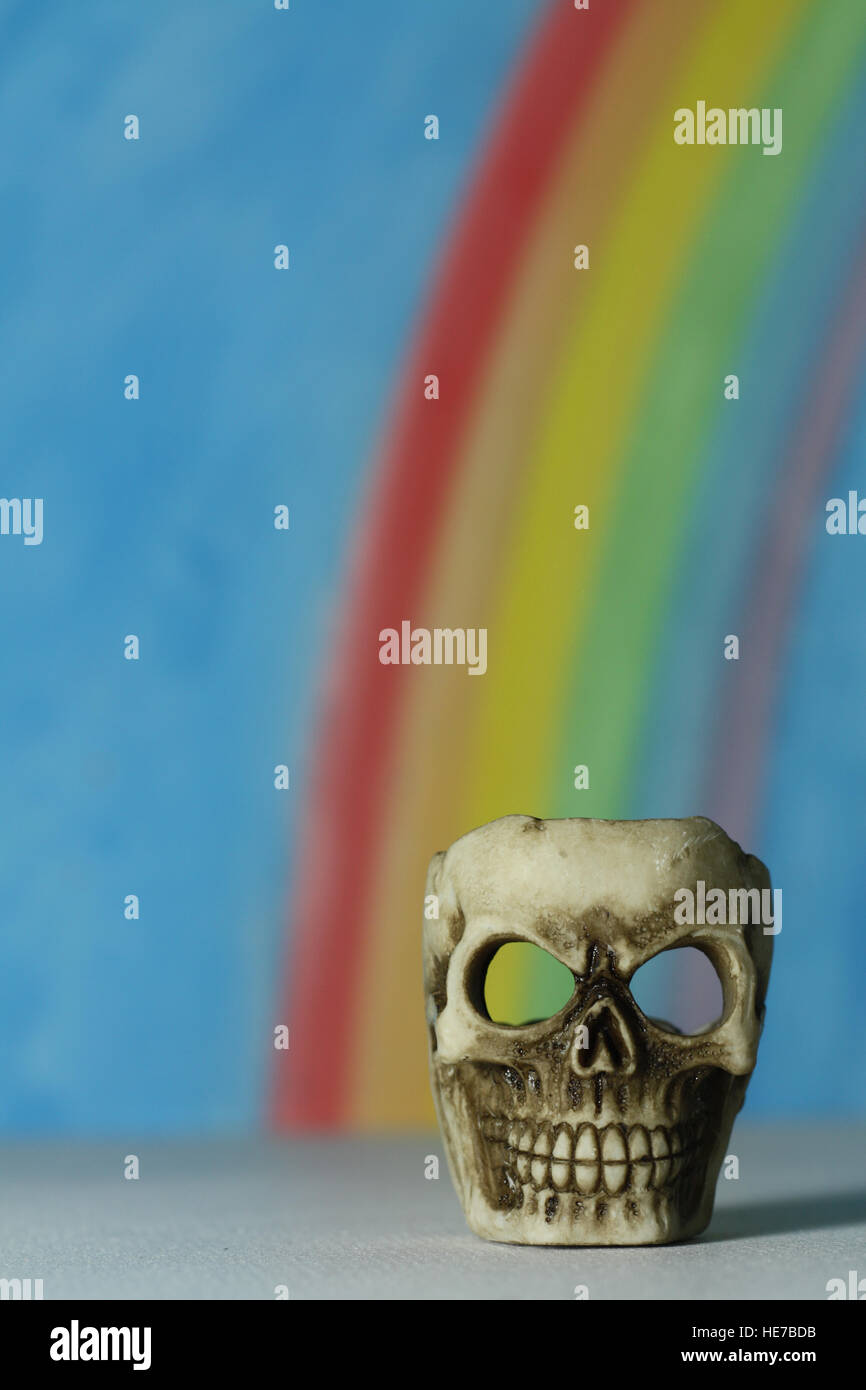 Human skull with a blue sky and rainbow background, a symbol of death, vanitas, horror and Yorick in Shakespeare's - Stock Image