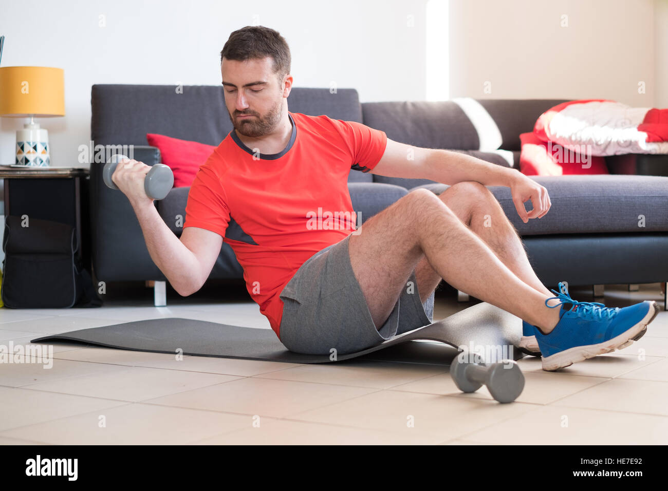 Man doing body exercise and working out at home - Stock Image