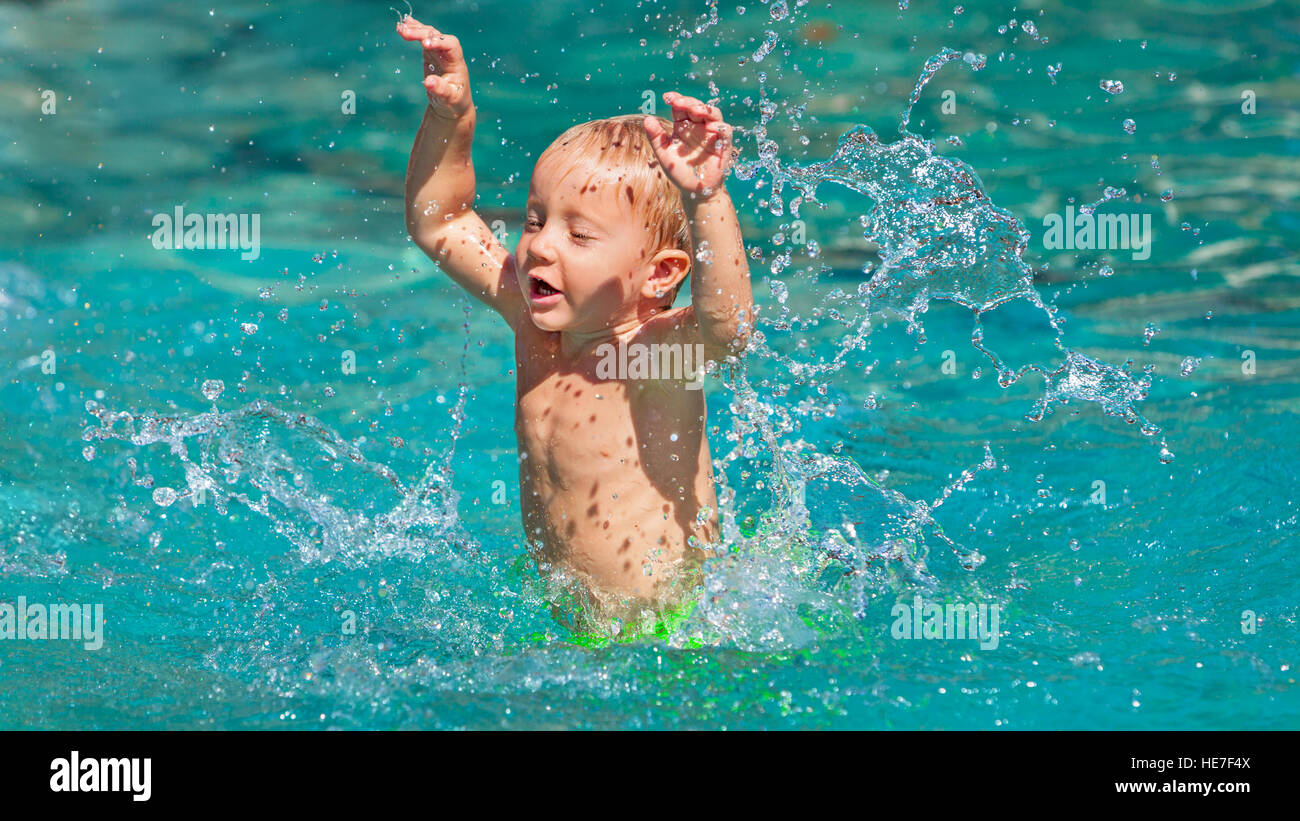Funny photo of active baby boy splashing in swimming pool with fun, jump deep down underwater. - Stock Image