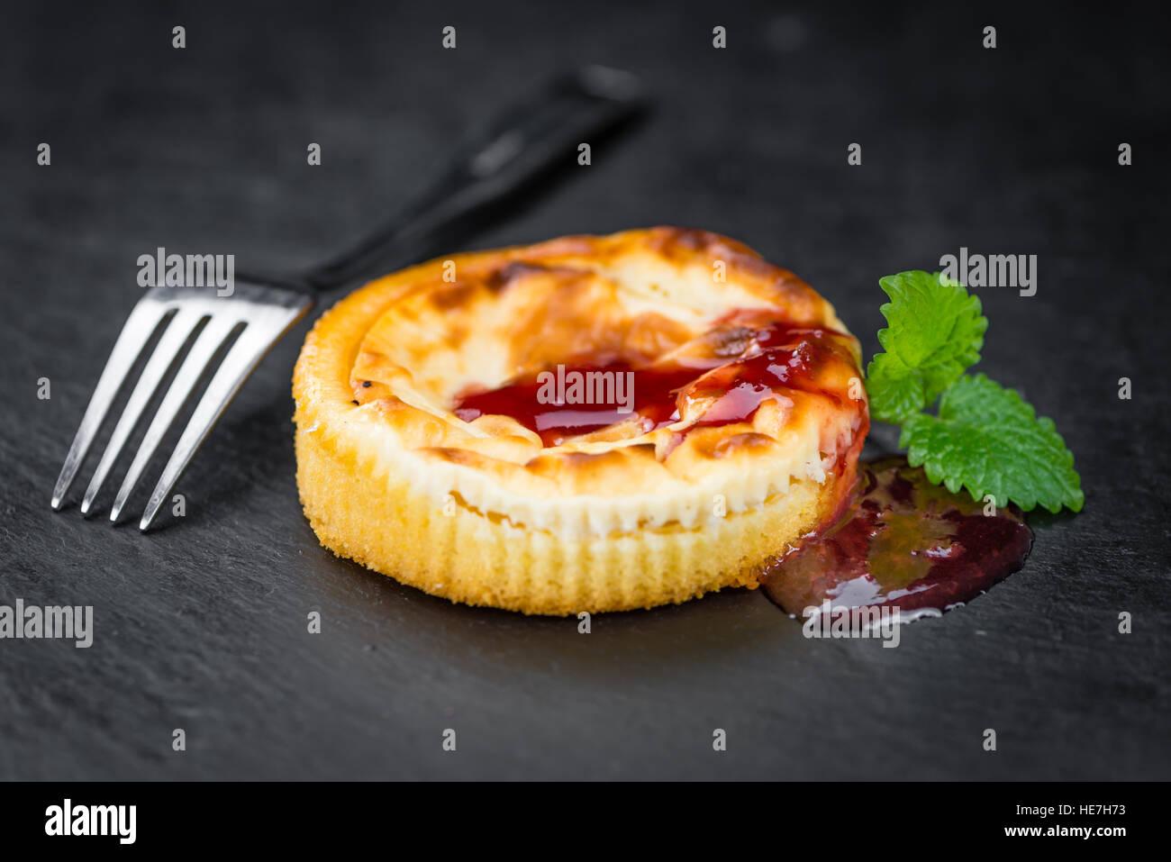 Fresh made Mini Cheesecake (with Sauce) on a vintage background (close-up shot) - Stock Image