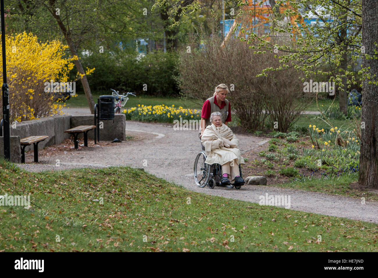 Elderly woman being helped by personal with outdoor access. - Stock Image
