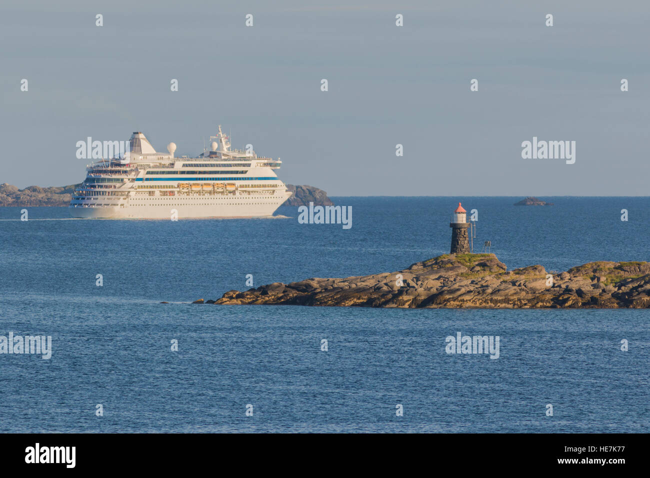 Cruise liner leaving port and going out to sea passing a lighthouse, Gravdal, Lofoten Islands, Norway - Stock Image