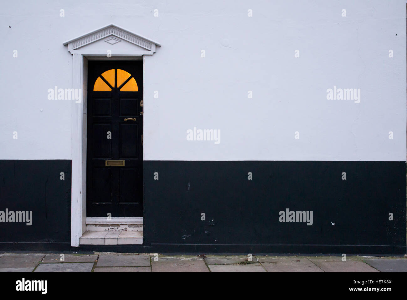 Black wooden Victorian door on a black and white wall with glass panel on top and warm yellow light coming from - Stock Image