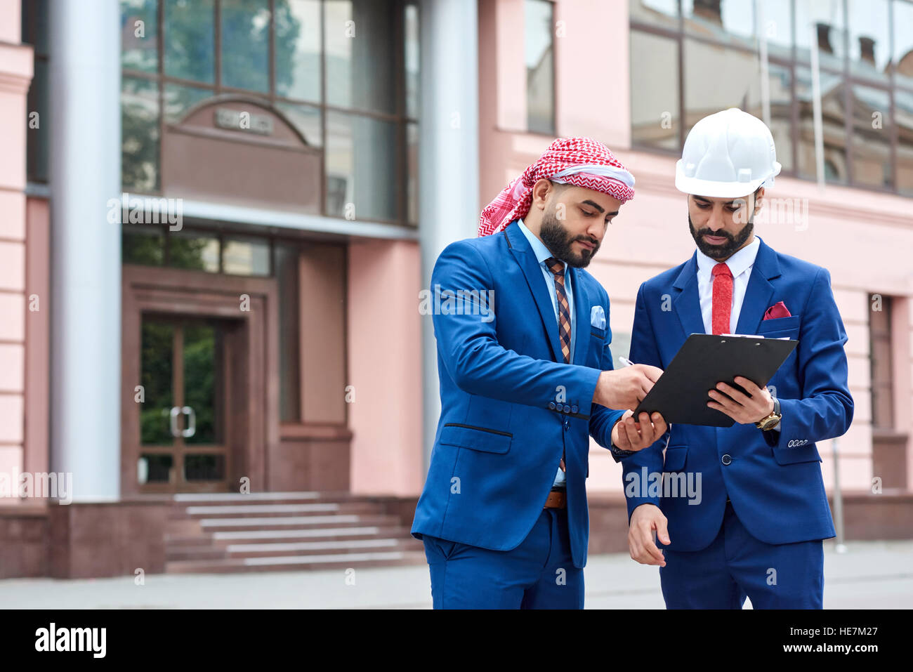 Your signature please. Portrait of a Saudi businessman signing papers with a professional engineer wearing a hardhat - Stock Image