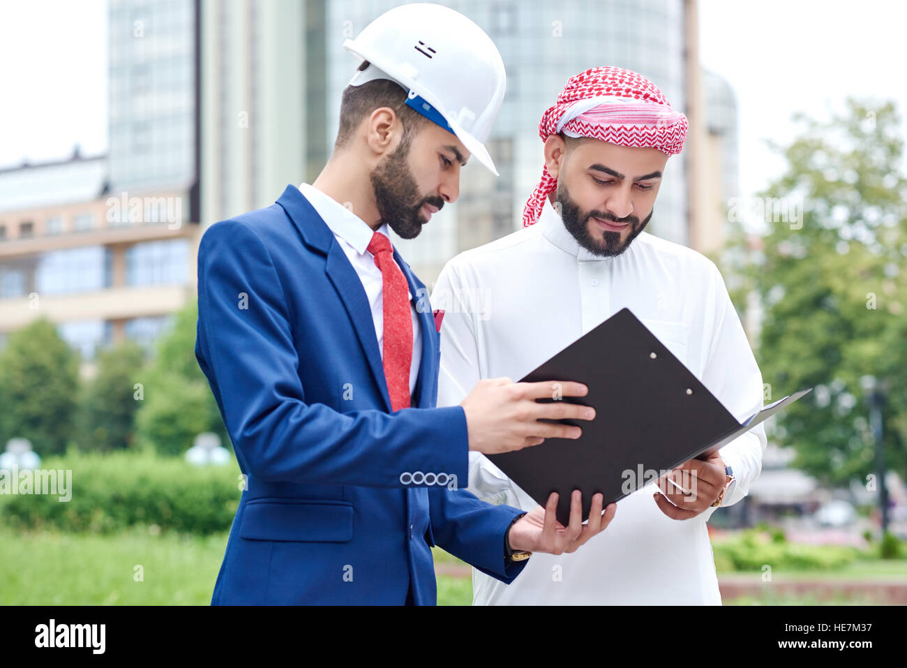 Signing the contract. Arab businessman checking contract papers with his architect - Stock Image
