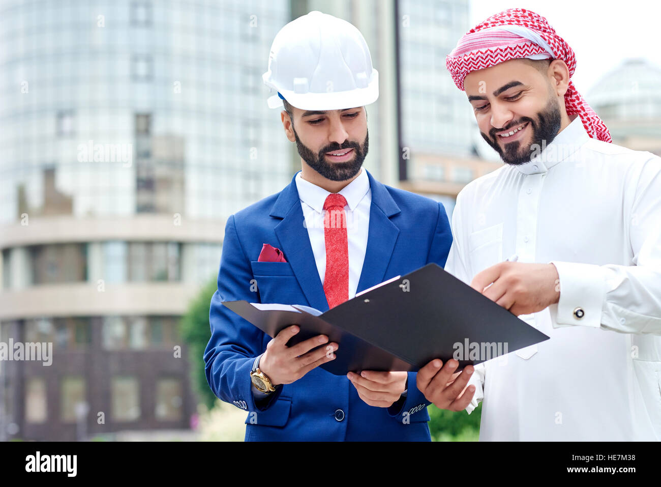 Concluding the deal. Horizontal portrait of an architect signing papers on a clipboard with his Saudi client - Stock Image