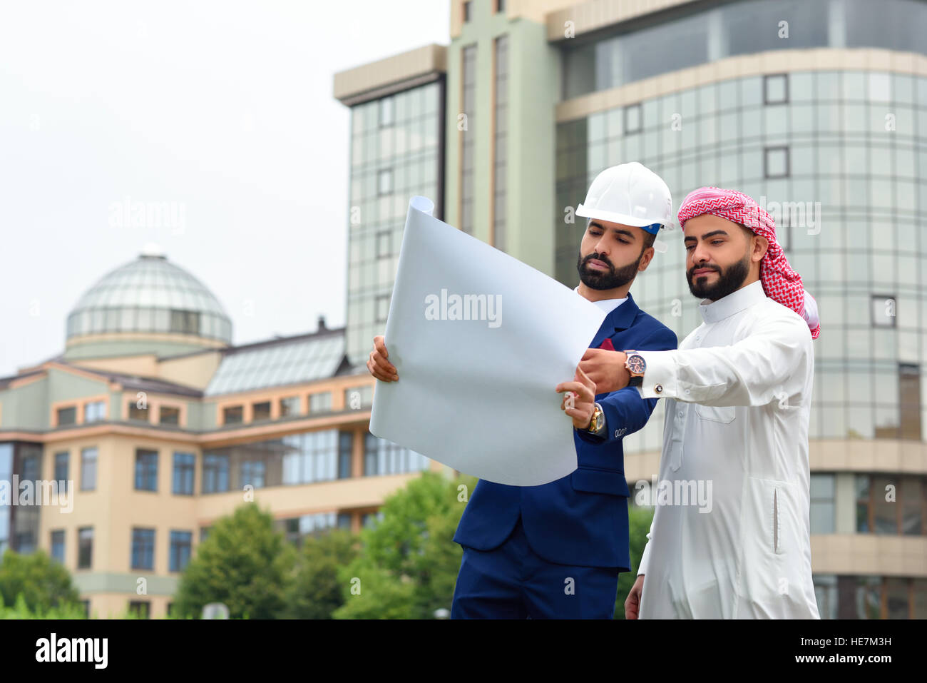 I see the future face of the city. Low angle shot of an architect discussing blueprints with his Saudi client copyspace - Stock Image