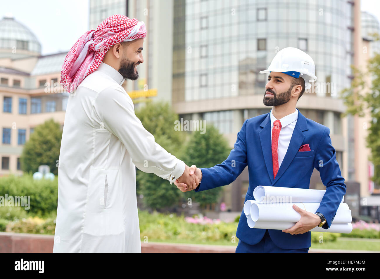 Total understanding. Portrait of a Saudi businessman shaking hands with an architect outdoors on the background - Stock Image